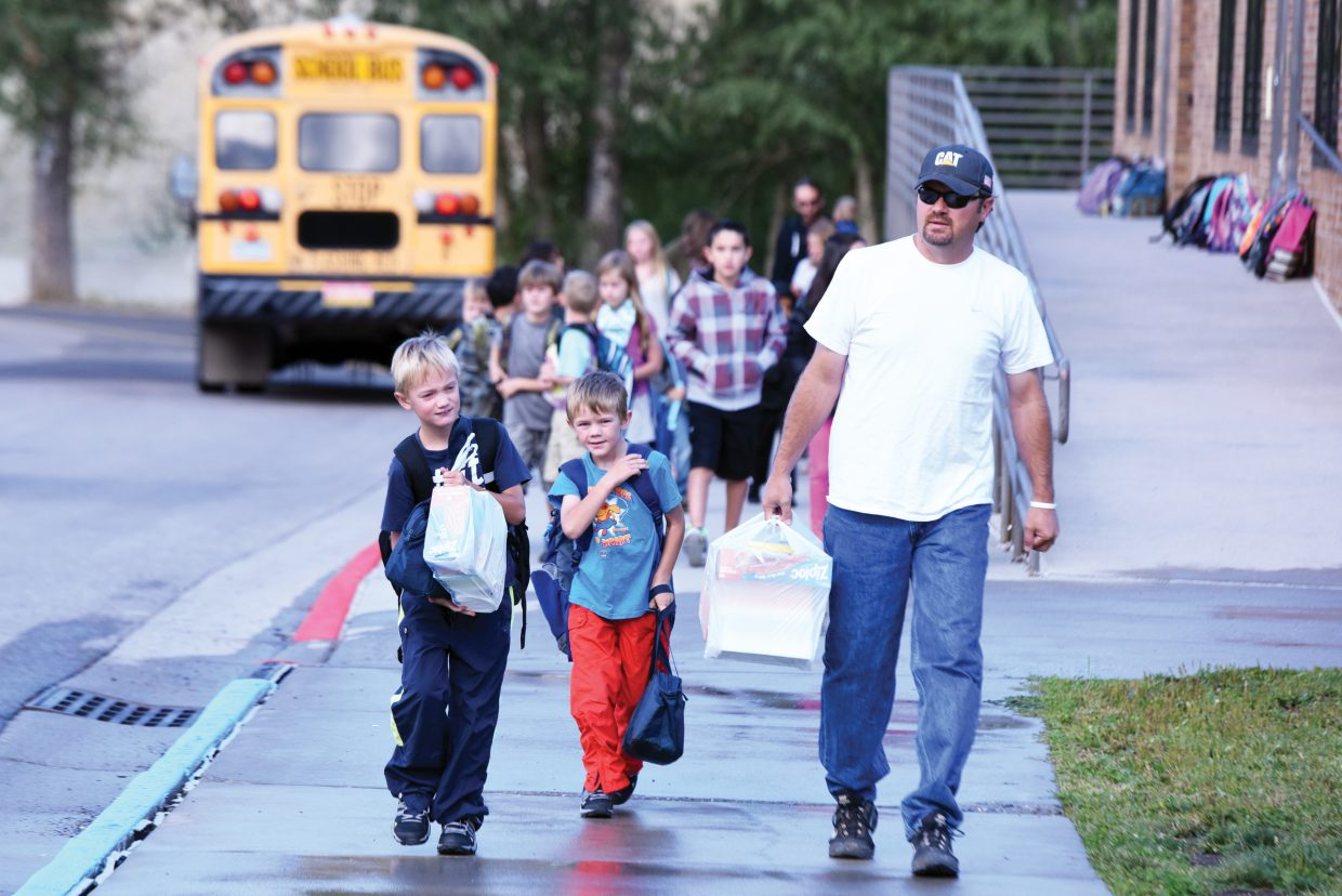 Mitch Locke escorts his sons, Marcus, far left, and Marshal, to Strawberry Park Elementary School for the first day of classes in Steamboat Springs. Schools in South Routt started Monday, and Hayden schools are slated to open the new year Thursday. Kindergartners in Steamboat Springs will return to class Wednesday.