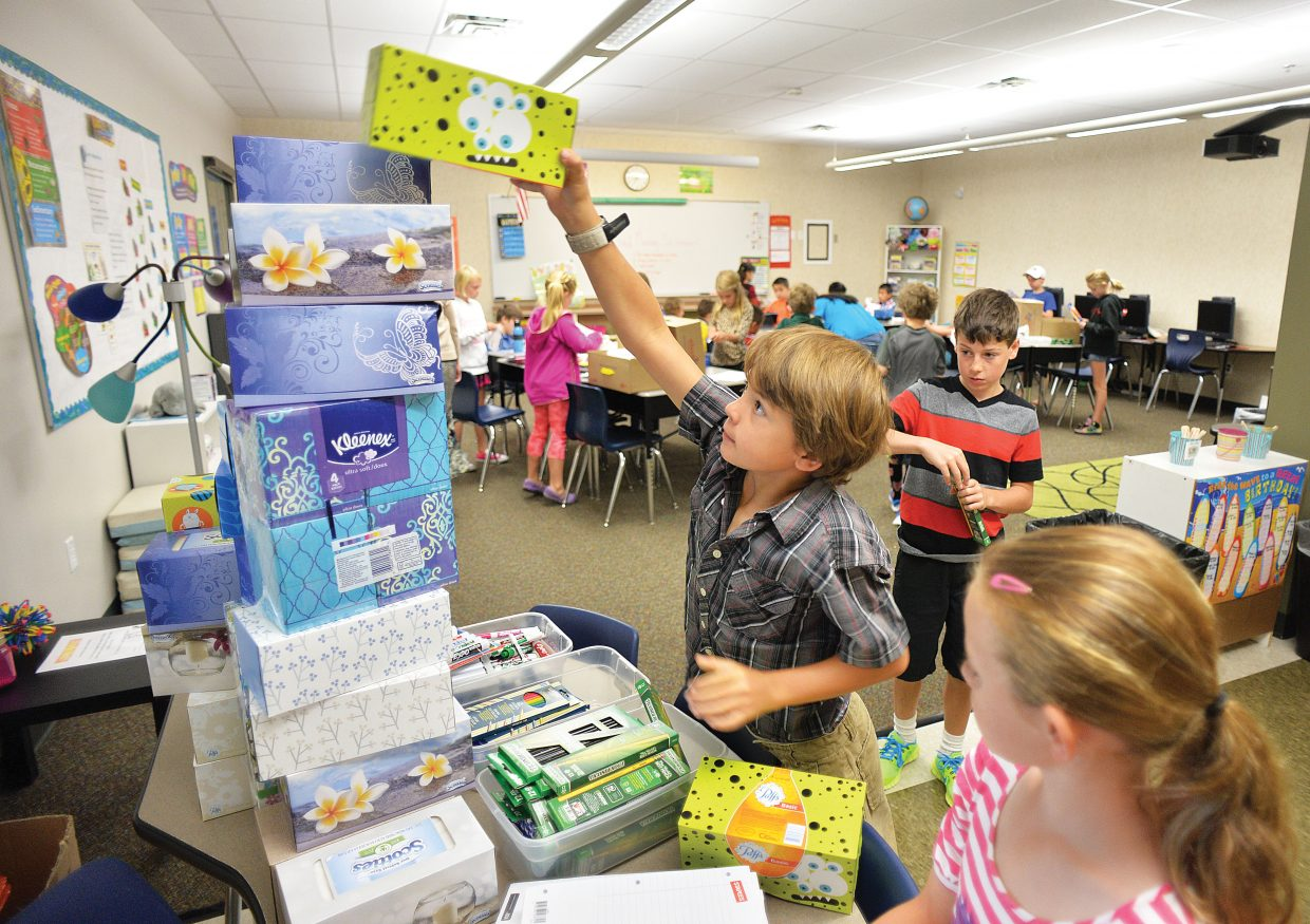 First-grader Grey Barbier stacks a Kleenex box onto of his classmates Tuesday morning at Soda Creek Elementary School. It was the start of a new school year in Steamboat Springs for first through 12th grades. The kindergartners will head to class Wednesday.