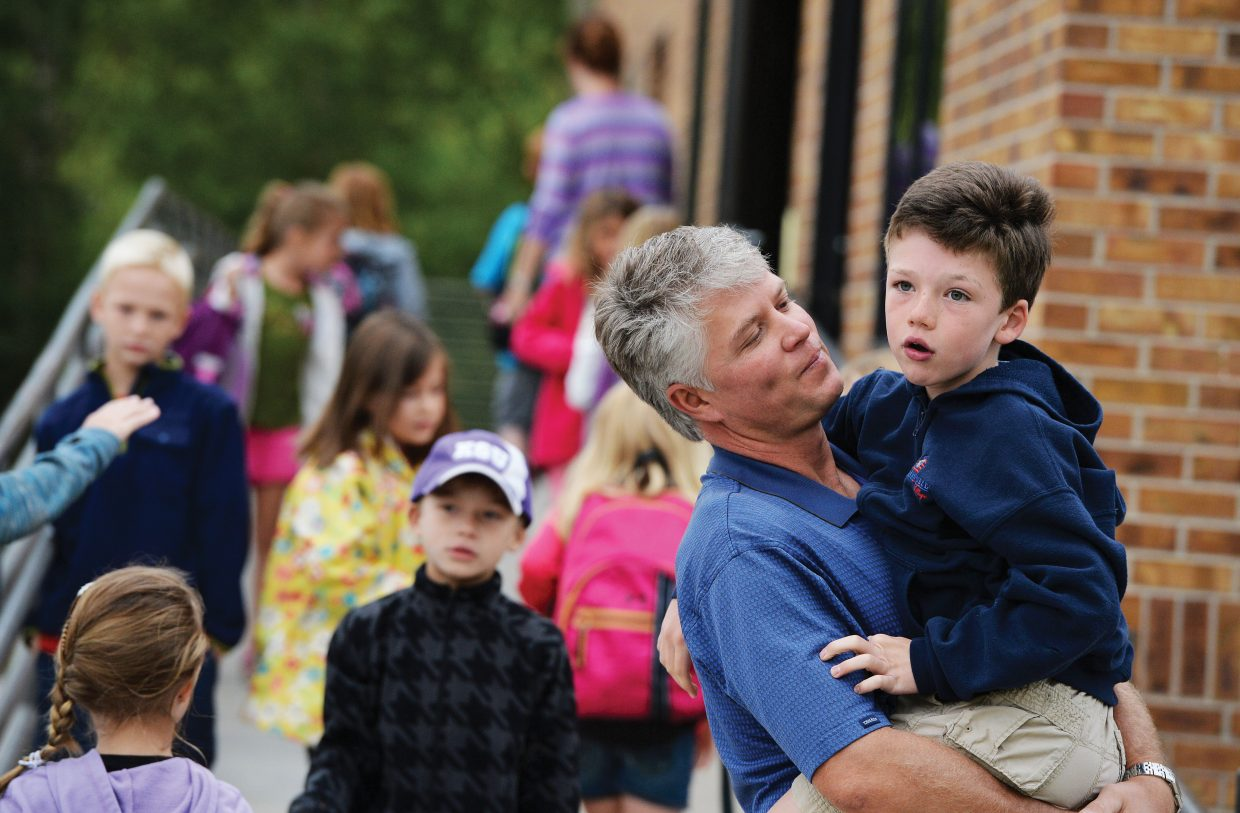 Second-grader Liam Siefken says goodbye to his dad, Todd, in front of Strawberry Park Elementary School on Tuesday morning.