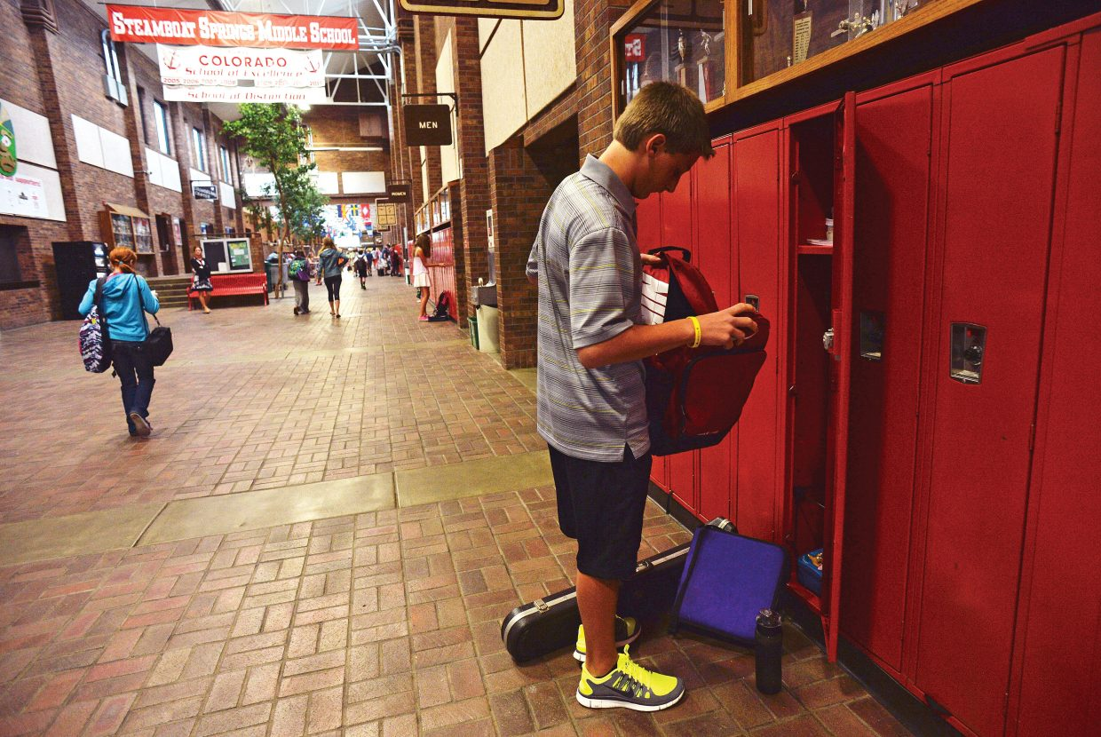 Steamboat Springs Middle School student Mac Moody unloads his backpack at his locker before heading to class Tuesday morning. It was the start of a new school year in Steamboat Springs for first through 12th grades. The kindergartners will head to class Wednesday.