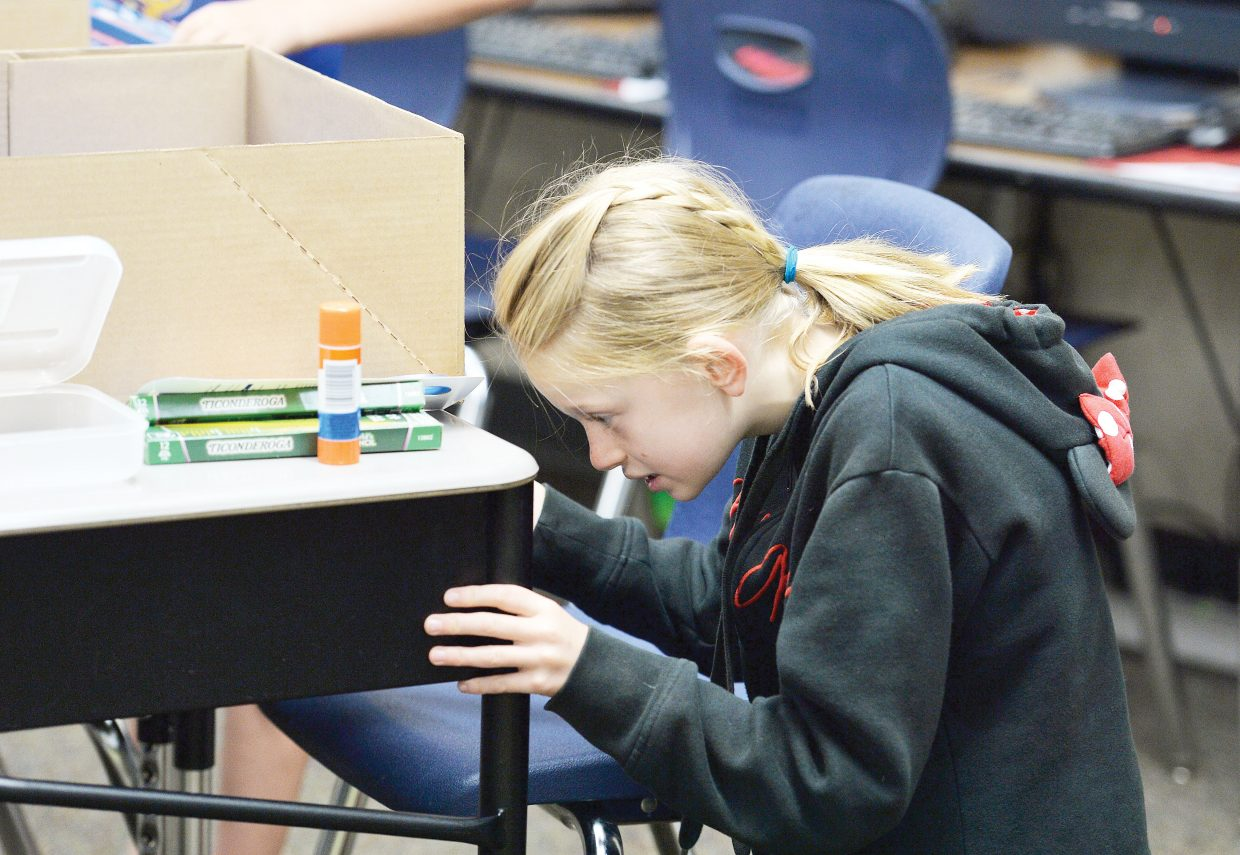 Third-grader Ashley Anfang puts her school supplies in her desk at Soda Creek Elementary School on Tuesday morning. It was the start of a new school year in Steamboat Springs for grades first through 12th. The kindergartners will head to class Wednesday.