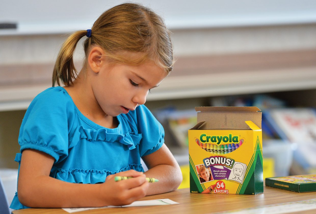 First-grader Eva Minotto uses a Crayon to decorate her name tag on the first day of classes at Soda Creek Elementary School. It was the start of a new school year in Steamboat Springs for grades first through 12th. The kindergartners will head to class Wednesday.