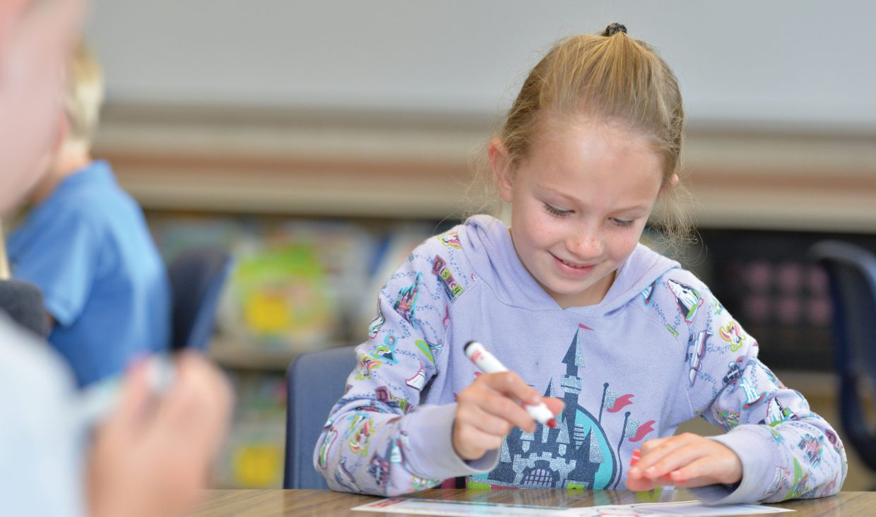 First-grader Zoe Anfang uses a marker to decorate her name tag on the first day of classes at Soda Creek Elementary School.