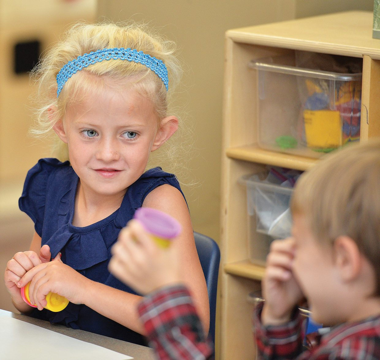 Kindergartner Kenzie Moore looks to a classmate while opening a can of Play-Doh during her first day of class at Soda Creek Elementary School Wednesday morning. Wednesday marked the first day of school for kindergartners in Steamboat Springs.