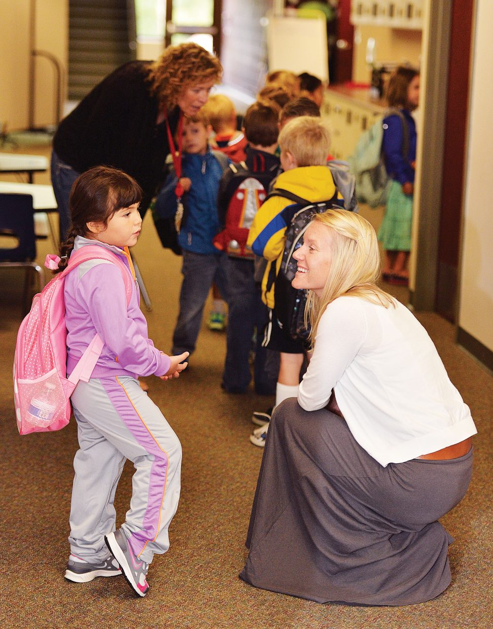 Kindergartner Remas Alnajdawi talks with counselor Emily Brust while waiting to go into her first day of class at Soda Creek Elementary School. While most of the school district began classes Tuesday, kindergartners didn't start classes until Wednesday.