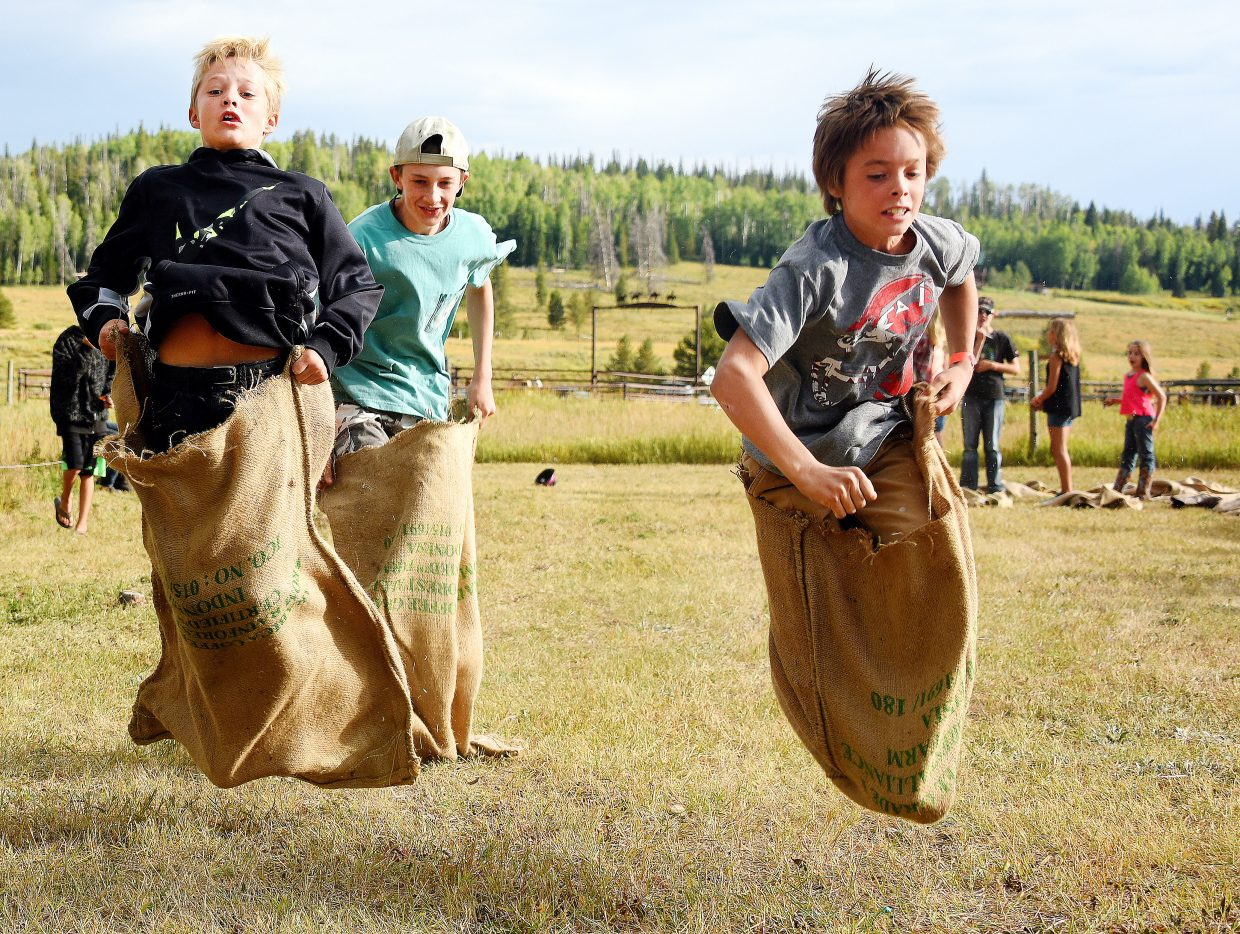 Hoppin' along: Cameron Daly, left, Bowden Tumminello and Pete Andersen charge toward the finish line in a sack race at Sunday's North Routt Community Barbecue at Hahn's Peak Roadhouse. In addition to sack races, the event included food, music, a silent auction benefitting North Routt Community Charter School and many other games and activities for children.