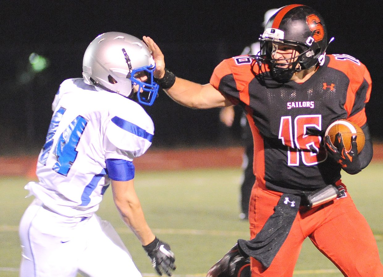 Steamboat's Zach Holm throws a stiff arm Friday against Moffat County.