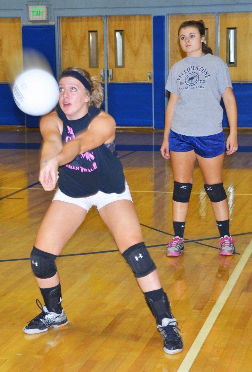 Moffat County High School volleyball player Maddy Olinger, left, steadies herself for a bump as Charli Earle waits for her own turn in a practice drill in the MCHS gym.