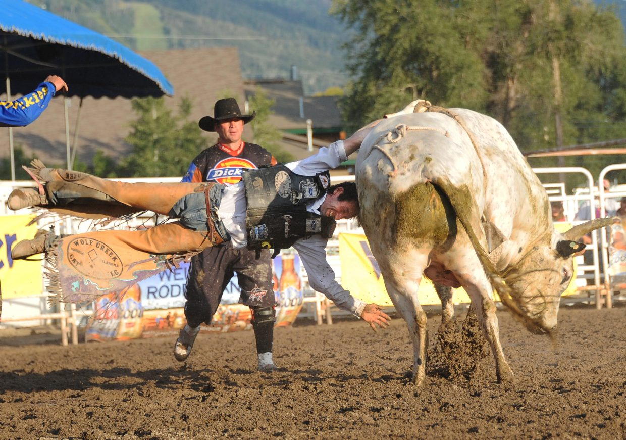 The bull Muddy Smile rips Ben Jones around by the arm Sunday during the PBR Bull Bash in Steamboat Springs.