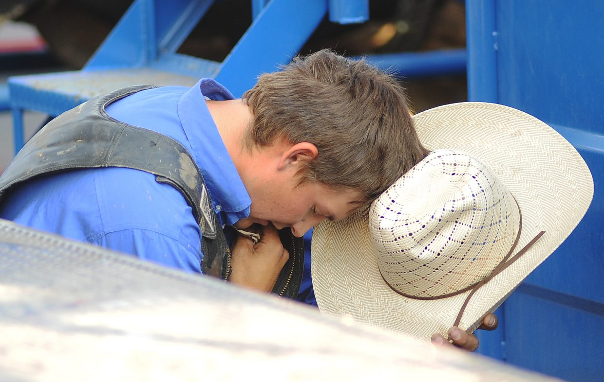A cowboy stops for a moment of silence before Sunday's PBR Bull Bash in Steamboat Springs.