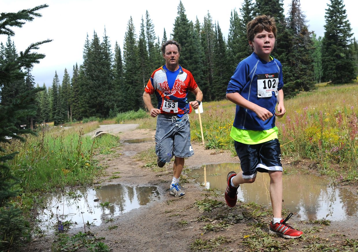 Jaydon Fryer and Darrin Fryer make their way down the muddy trail Sunday during the 10K at 10,000 Feet on Rabbit Ears Pass on Sunday. The Steamboat Springs Running Series race drew about 120 finishers.