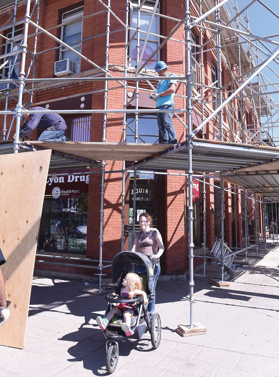 Jennifer Camlet and her daughter, Shelby, make their way down the sidewalk as workers Louis Cruz, kneeling, and Thomas Hernandez, of Colorado Scaffolding, erect platforms in front of the Squire Building that houses Lyon's Drug and several other businesses on Lincoln Avenue in downtown Steamboat Springs. The owners of the building will be doing some maintenance on the building's stone work.