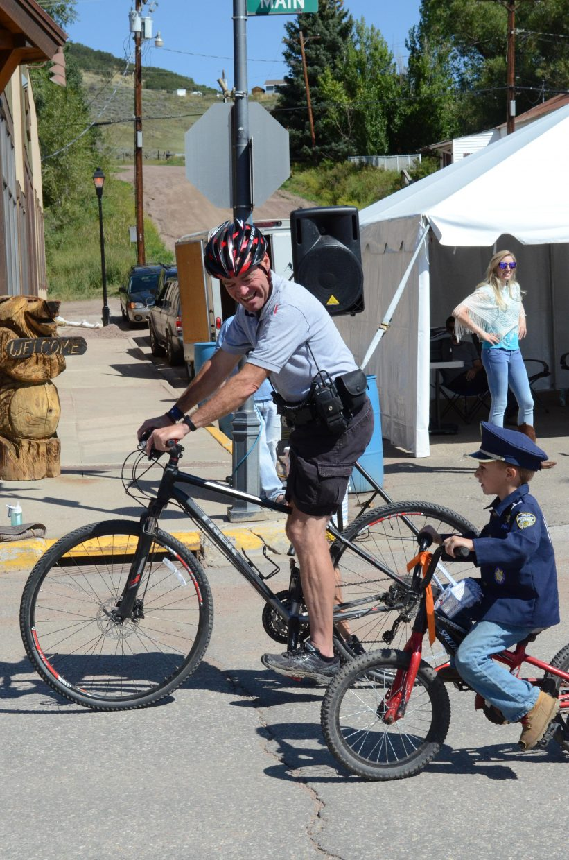 Oak Creek police officer Bobby Rauch and his young sidekick, Jace Wisecup, cycled down Main Street as part of Monday's Labor Day parade.
