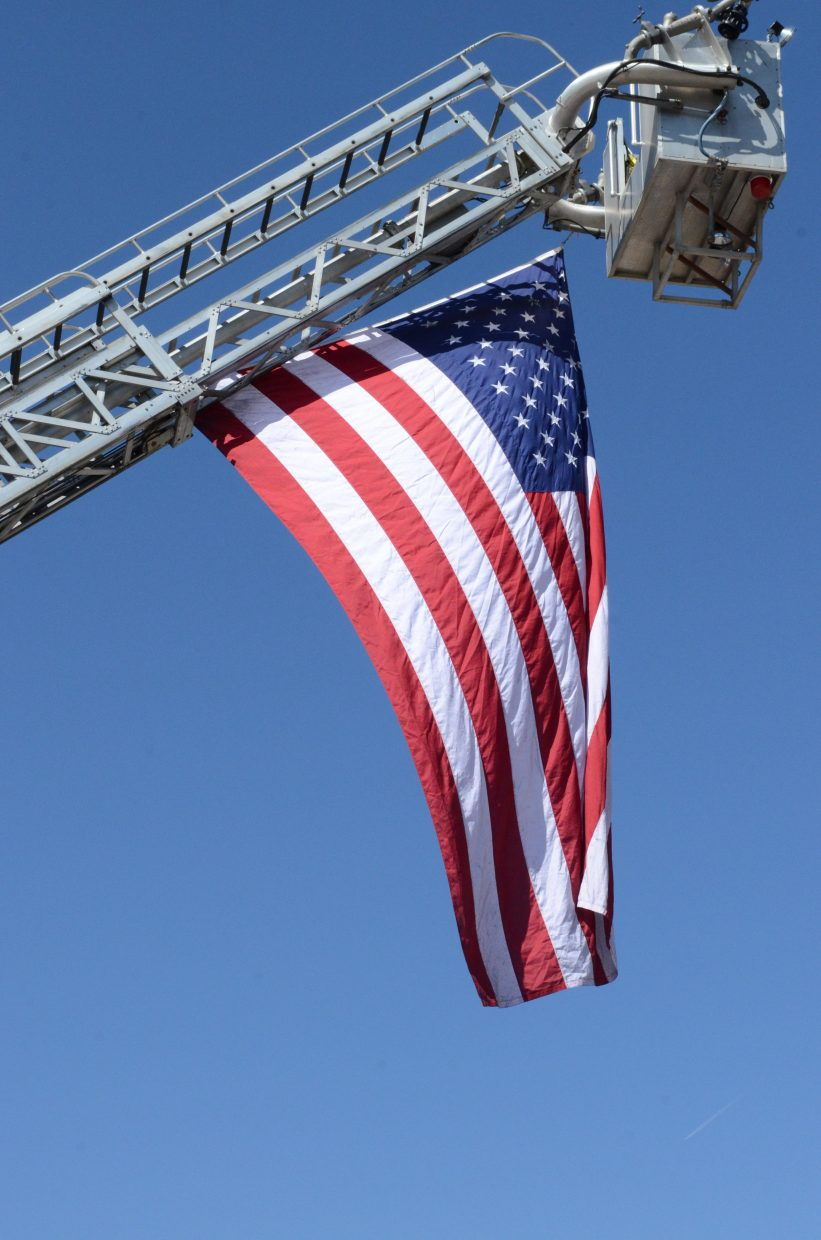 A huge American flag, suspended by a hook and ladder fire truck, waved over Oak Creek's Main Street during the annual Labor Day parade Monday.