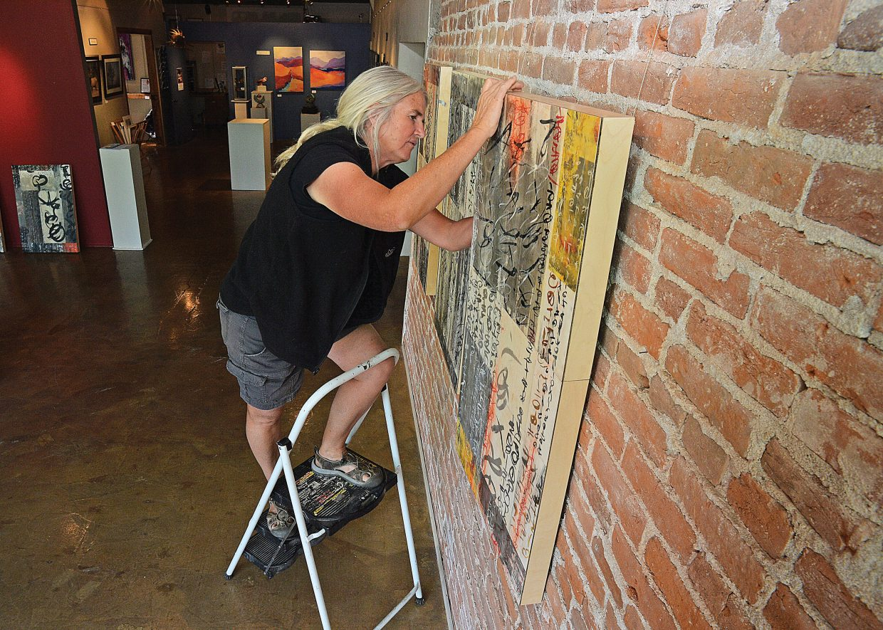 Artist Laura Wait hangs her work at the Circle 7 Fine Art gallery in Steamboat Springs. Wait will be featured this month at the downtown gallery.