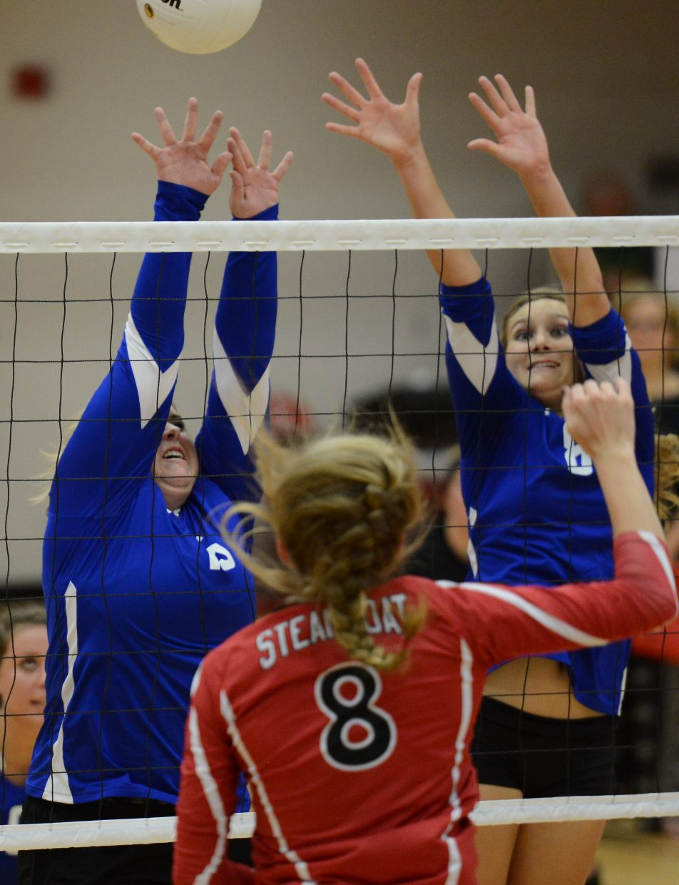 Steamboat's Riley Wilkinson tries to push a ball through a block with Moffat County's Alexi Goodnow, left, and Britney Rothermund.