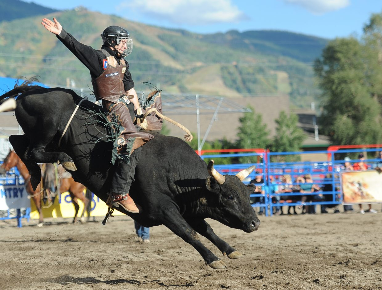 A cowboy hangs on during Sunday's Rocky Mountain Bull Bash bull riding event in Steamboat Springs.