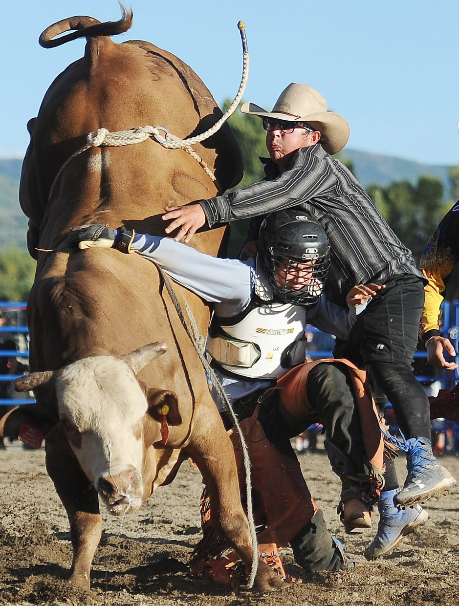 A bull fighter reaches to try to help an entangled cowboy Sunday at the Rocky Mountain Bull Bash in Steamboat Springs. The bulls tossed plenty of the evening's cowboys, but Hayden's Kaiden Decker rode both of his bulls to win the event.