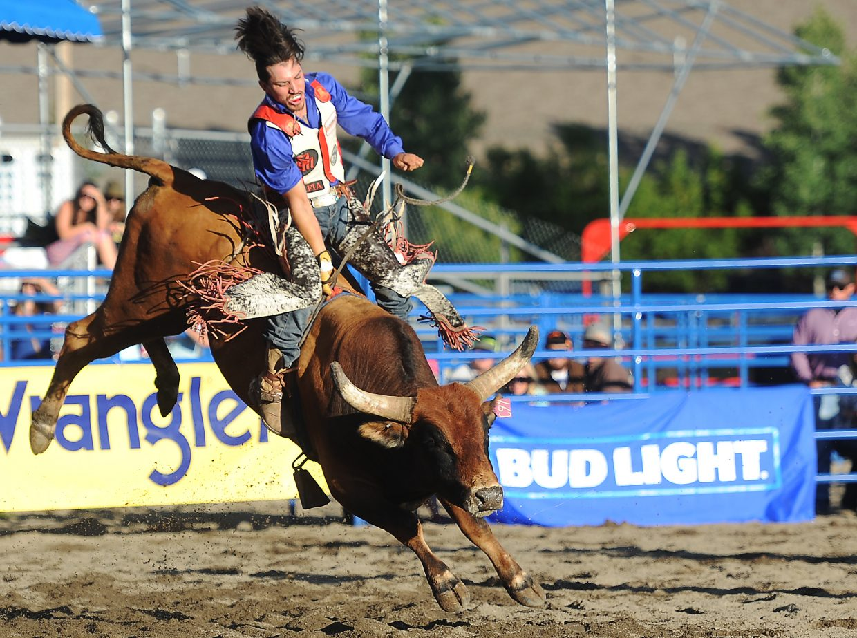 Eric Cordova hangs on tight during Sunday's Rocky Mountain Bull Bash event in Steamboat Springs.