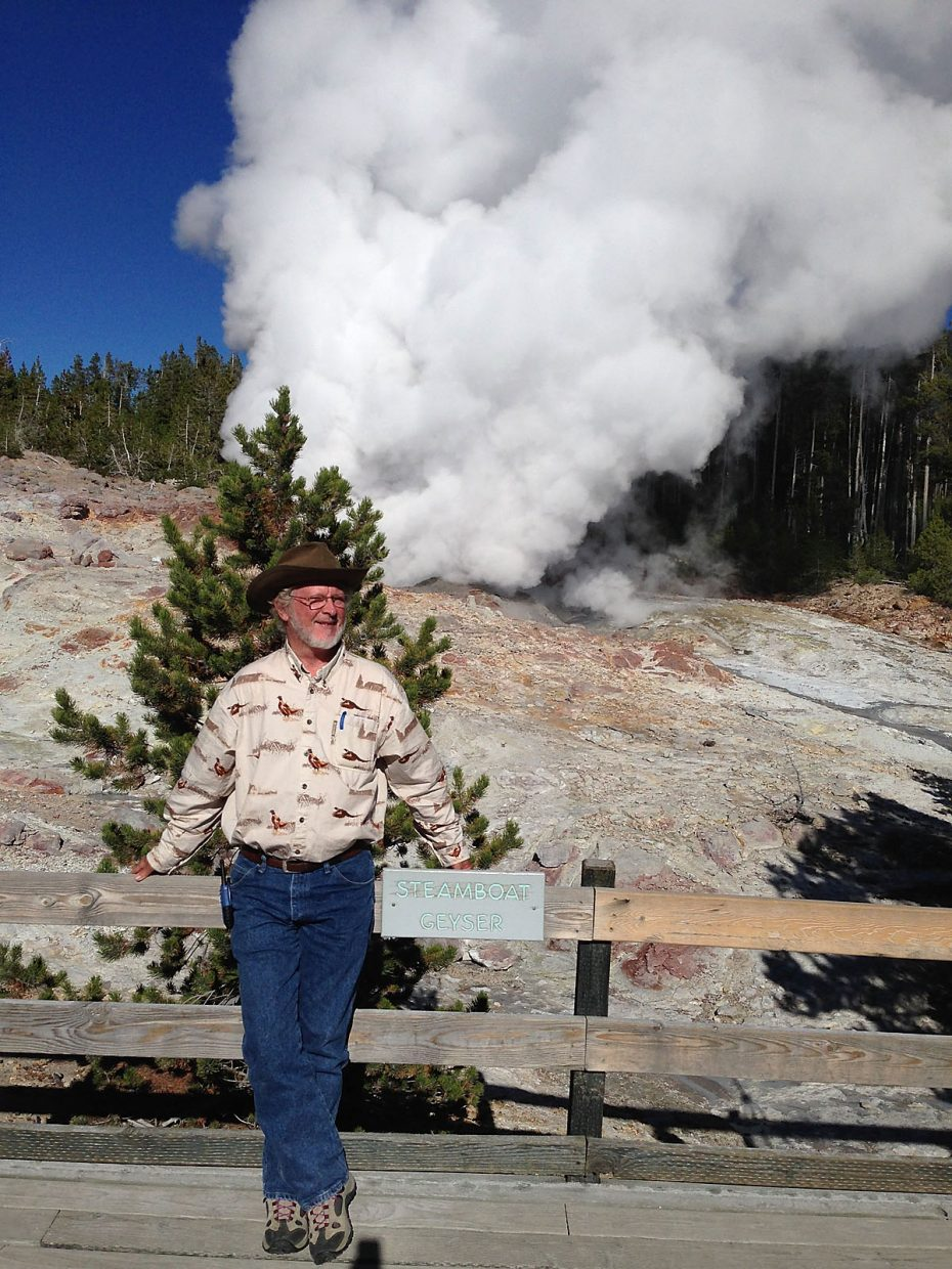 Colorado Mountain College biology professor Shawn Sigstedt, on sabbatical from the Alpine Campus in Steamboat Springs, poses in front of the rare sight of the Steamboat Geyser venting a roaring column of steam in Yellowstone National Park this week. Sigstedt joined the Geyser Gazers group three years ago.