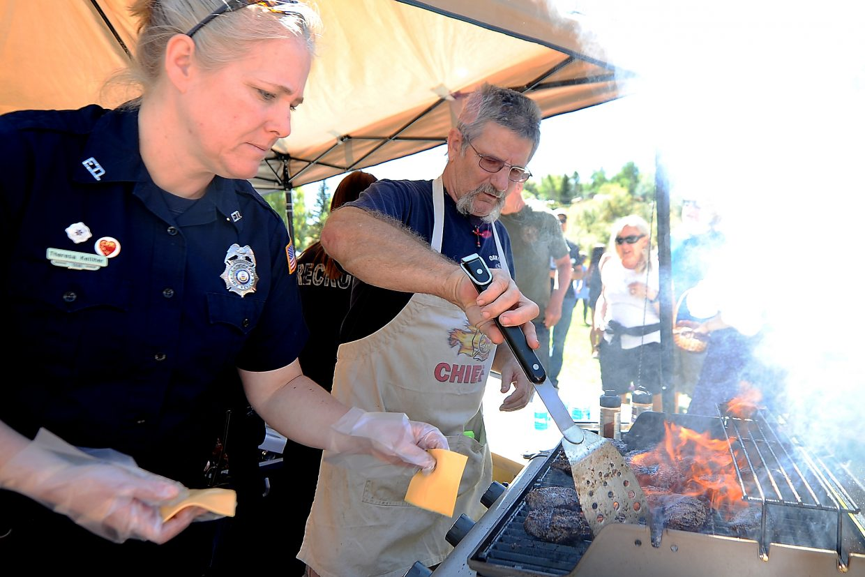 Oak Creek Fire Protection District Chief Chuck Wisecup manages the burgers while Oak Creek EMT worker Theresa Kelliher lays on the cheese Monday during the Oak Creek Labor Day celebration. The Oak Creek Fire Protection district ran a small booth serving food in Decker Park. The day included a parade through the town, followed by games and activities in Decker Park.