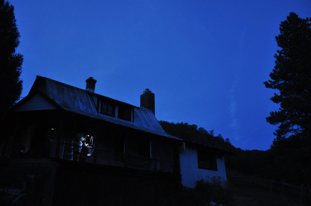 Using headlamps, bat researchers check the bat traps on the front porch of the Rehder Ranch.