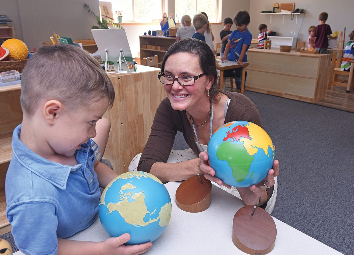 Evan Dendrinos, a kindergartner at Mountain Village Montessori Charter School, works with teacher Jessica LeBlanc Tuesday on the school's first day of classes.