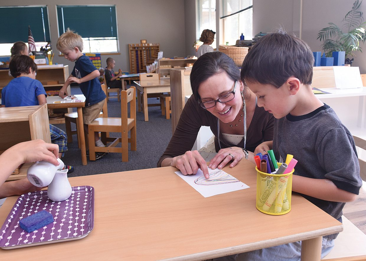 Trevon Shoemaker, a kindergartner at Mountain Village Montessori Charter School, works with teacher Jessica LeBlanc Tuesday on the school's first day of classes in September.