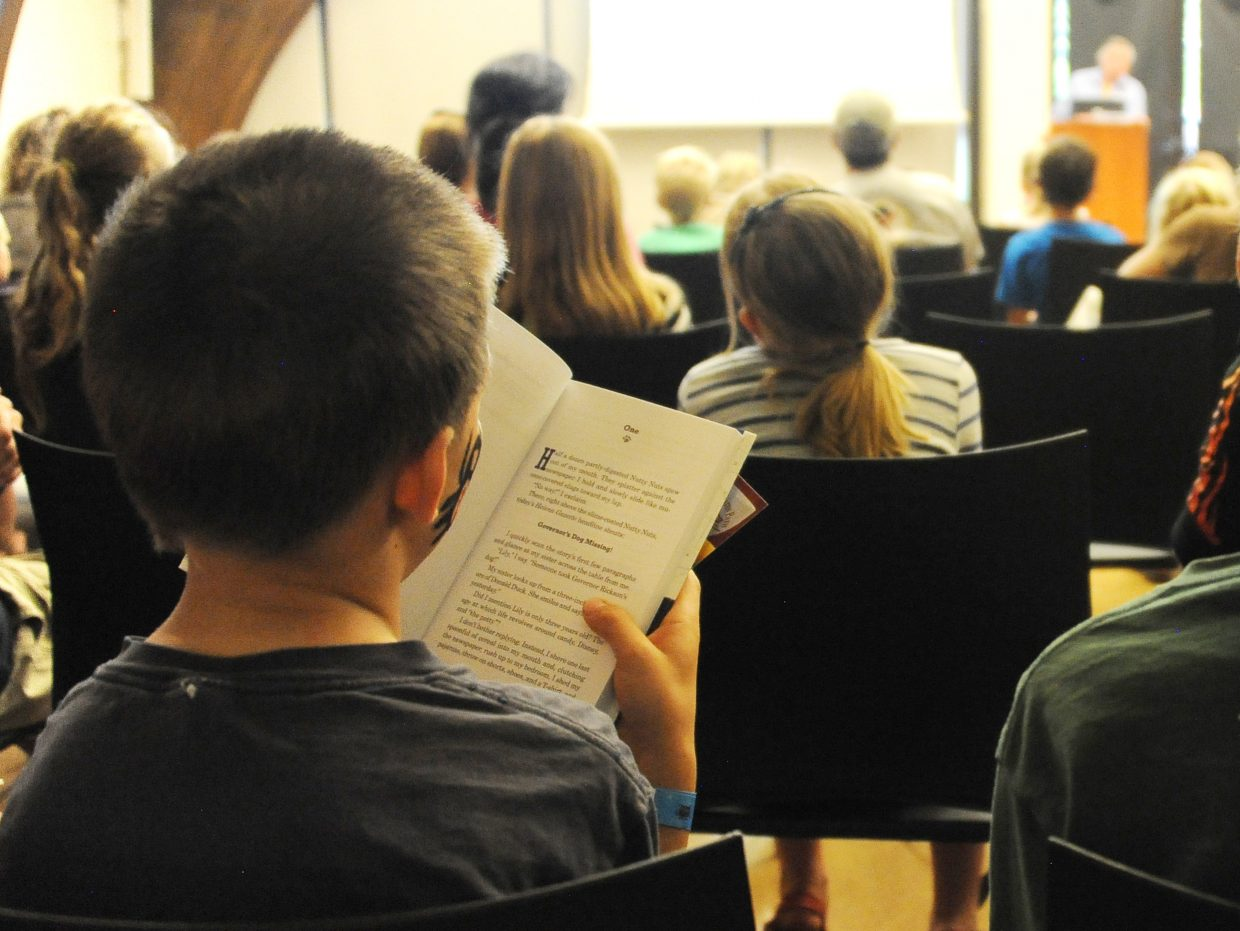 Ryan Drennan, 9, reads during a lecture in downtown Steamboat Springs. It may say something negative about a speaker elsewhere, but at the Book Feast festival at Bud Werner Memorial Library, reading a book by Avi while Avi is speaking goes down as a big compliment. Avi will be one of the authors featured again at the third annual Children's Book Feast on May 9.