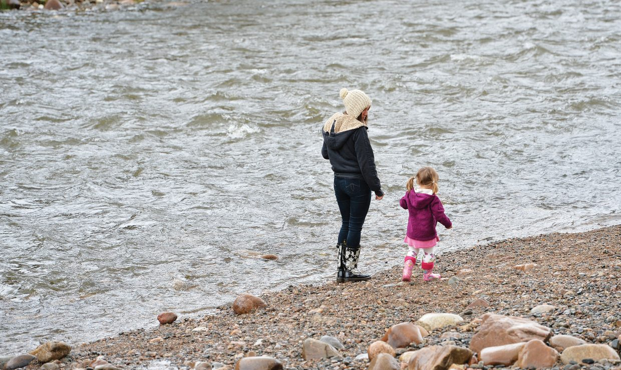Tuesday's rainy, fall-like weather wasn't enough to keep Hallie Chabot, 2, or her mom, Marie, inside. The pair grabbed their jackets, Boggs boots and hats before heading out to the banks of the Yampa River, where they enjoyed throwing rocks into the water.