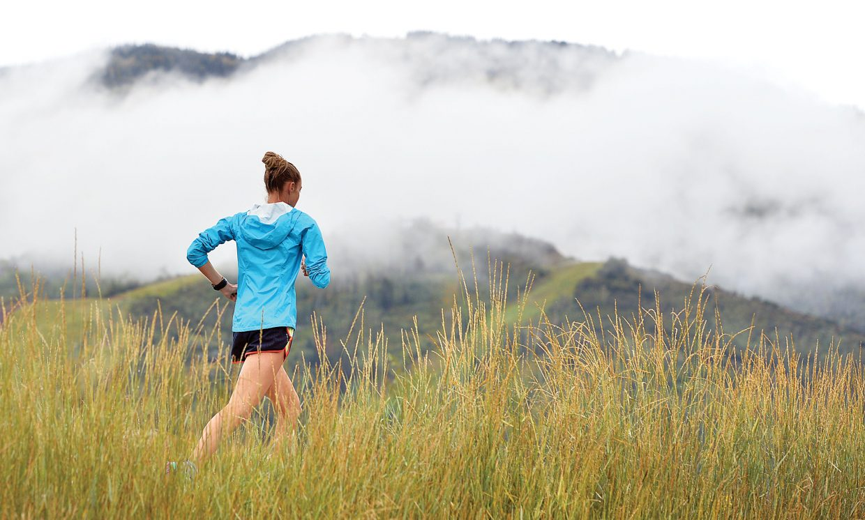 A runner didn't let Tuesday's rainy weather keep her from running along the Yampa River Core Trail, even as storm clouds in the background shrouded Mount Werner.