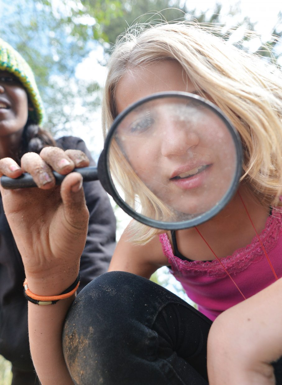 Sixth-grader Rosalie Mortensen uses a magnifying glass during the Yampa Valley Science School on Wednesday afternoon at the Perry-Mansfield Performing Arts School and Camp near Steamboat Springs. The camp will host students from Steamboat Springs, Emerald Mountain, South Routt and North Routt in the next few weeks.