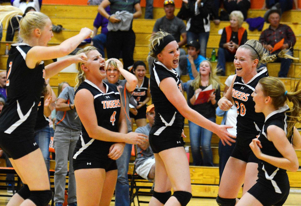 The Tigers celebrate after knocking off West Grand on Thursday in five sets.