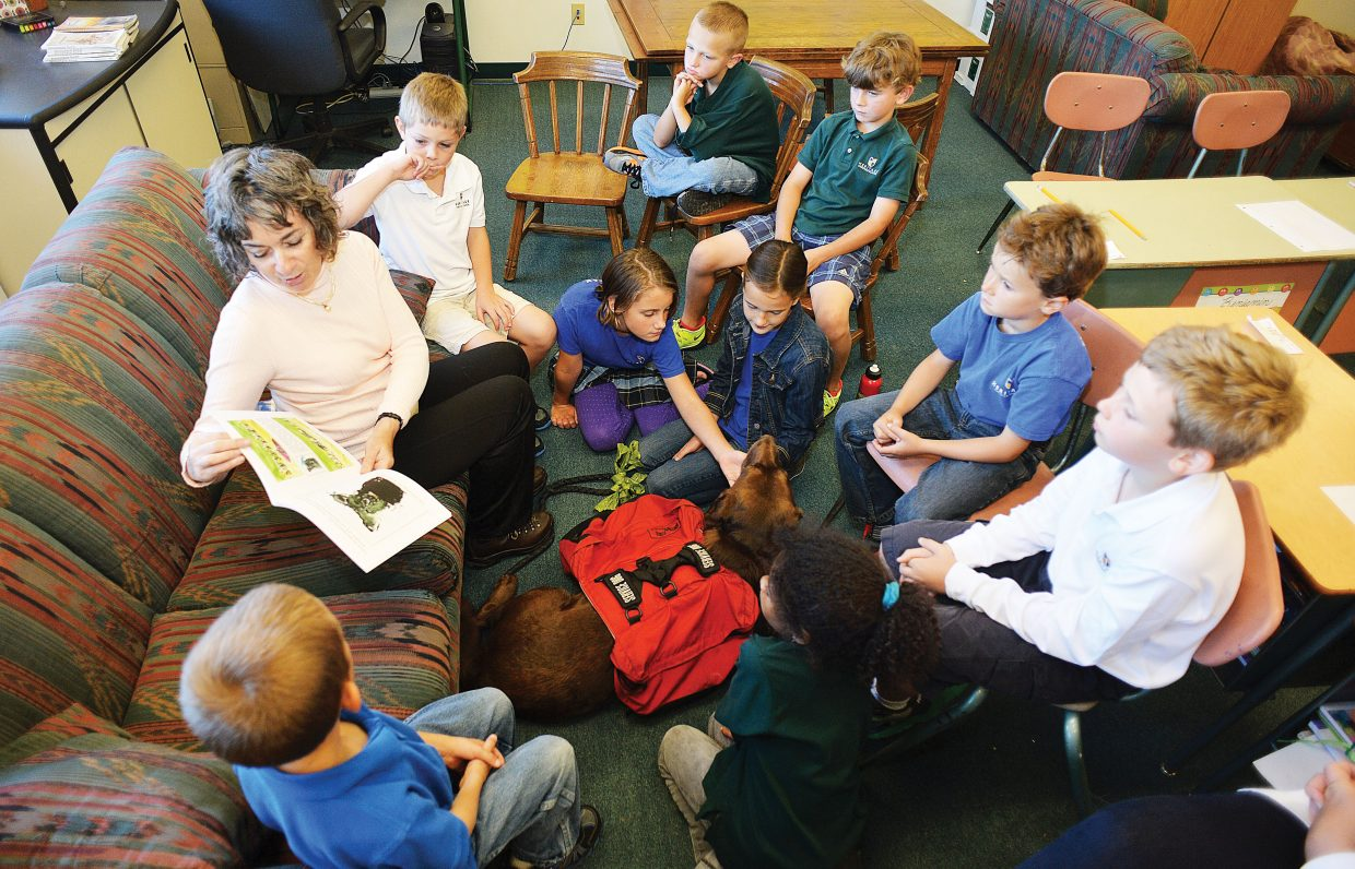 """Author Trish Carpenter reads her book, """"The Stray Who Became a Service Dog"""" to Lauri Bradt's class of third and fourth grade students at Heritage Christian School on Friday morning. Carpenter visited the school along with her own service dog."""