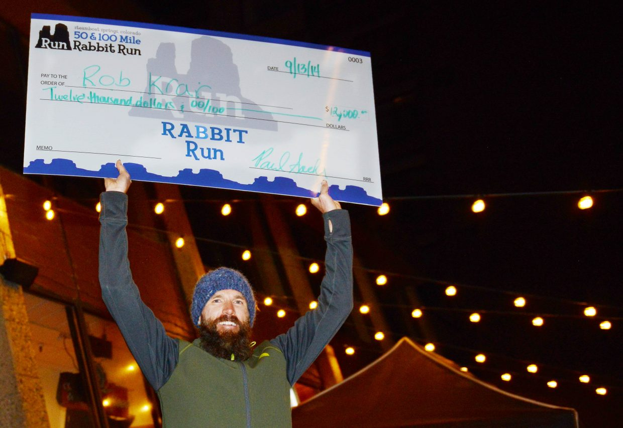 Rob Krar holds up his first-place check for $12,000 on Saturday night at the awards ceremony for the Run, Rabbit Run 100-mile race. Krar launched away from the field midway through the race to win the event and add it to his already long list of ultra-running victories. The event, which raises funds for local charities, annually draws elite runners with the largest prize purse in the ultra trail-running industry.