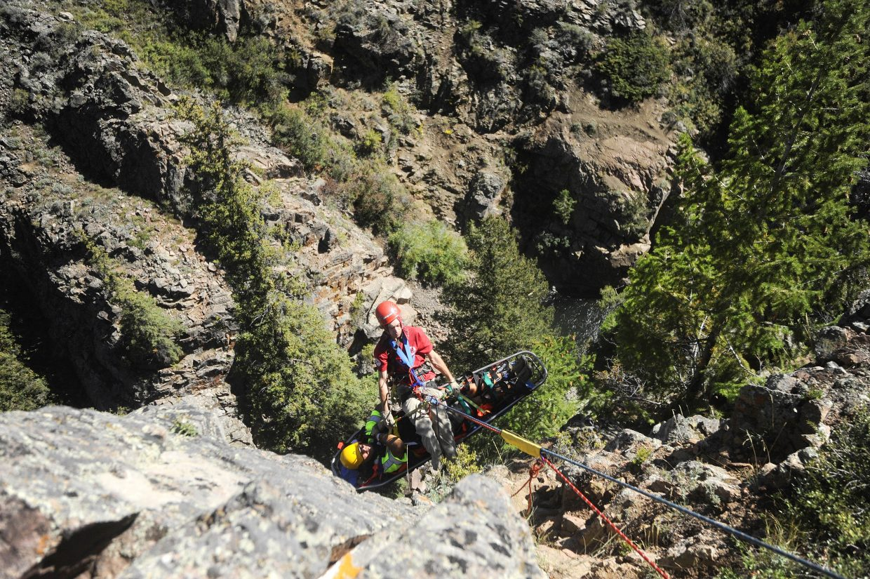 Dalton Reed brings up his mock patient, Ty Upson, in the rescue basket above King Solomon Falls.
