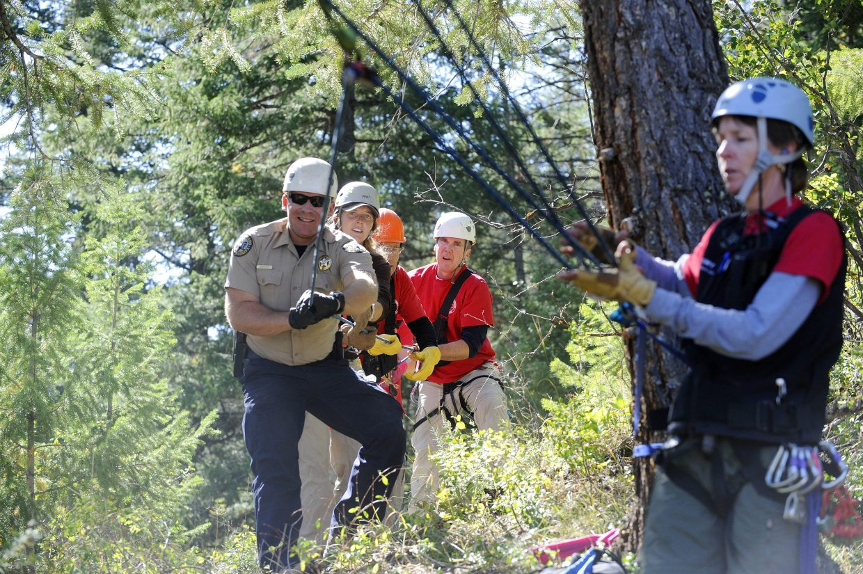 Kristia Check-Hill, front, works a complicated rope system with Colorado Parks and Wildlife ranger Robert Seel, Brittany Letendre, Jim Linville and Russ Sanford.