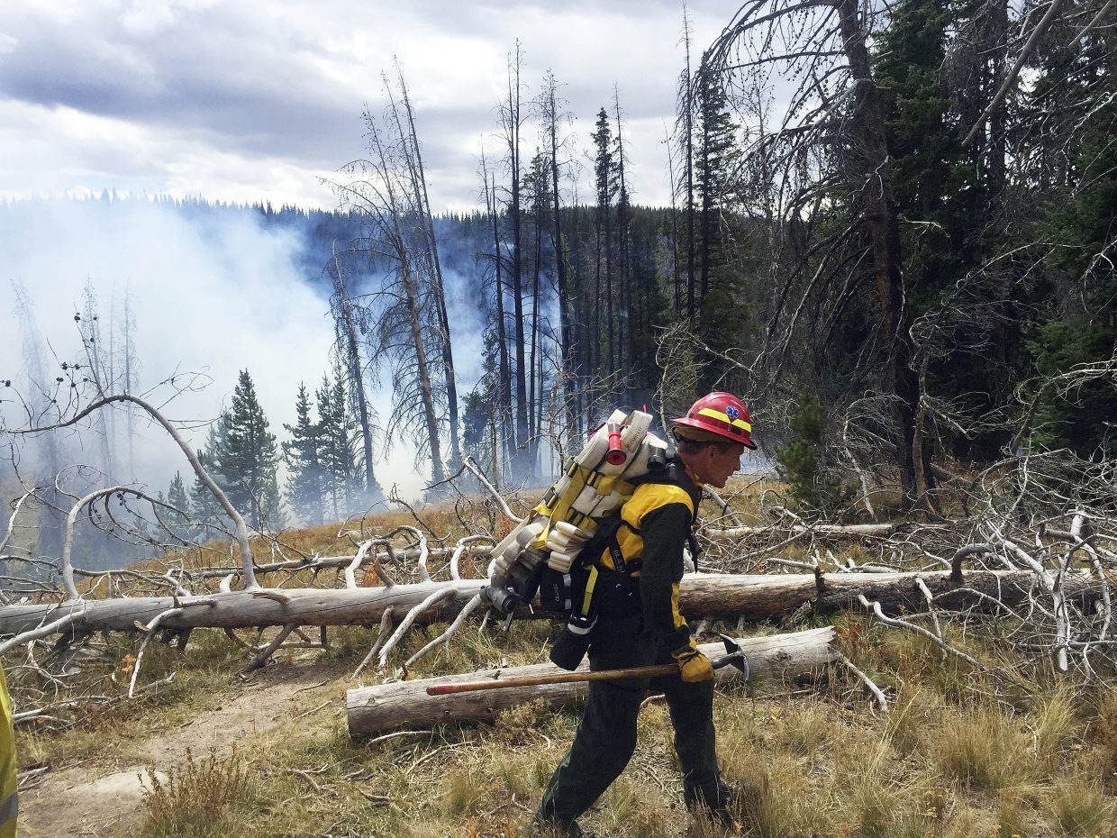 Steamboat Springs Fire Rescue firefighter Matt Mathisen hikes to a wildfire that ignited Wednesday on Rabbit Ears Pass near the Walton Peak trailhead. The quarter-acre fire was started by an abandoned campfire and was put out.