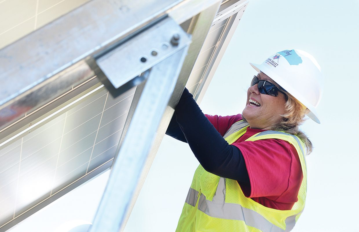 Yampa Valley Electric Association employee Kathy Bertrand fastens a solar panel to its supports Friday while volunteering to help build a new solar array near YVEA's new headquarters on Routt County Road 129 in Steamboat Springs.