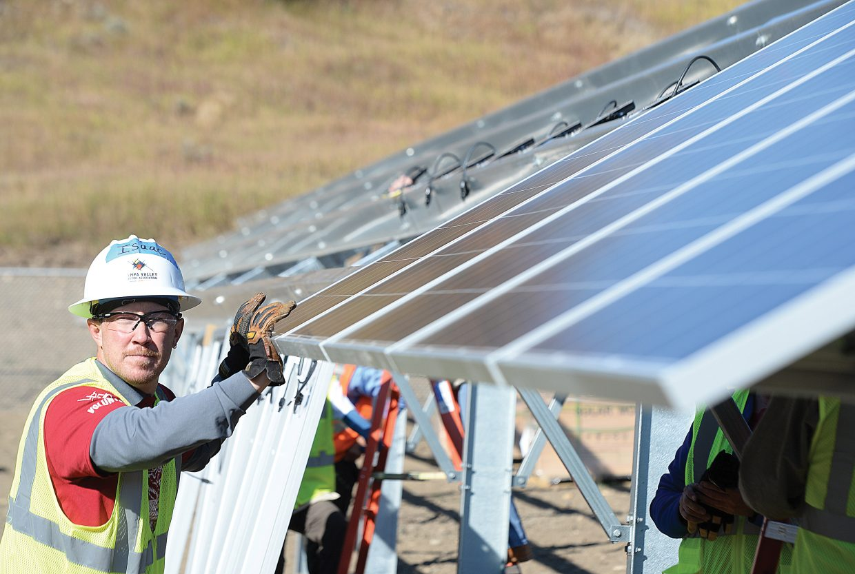 Yampa Valley Electric Association employee Isaac Nichols positions solar panels Friday while volunteering to help build a new solar array near YVEA's new headquarters on Routt County Road 129 in Steamboat Springs.