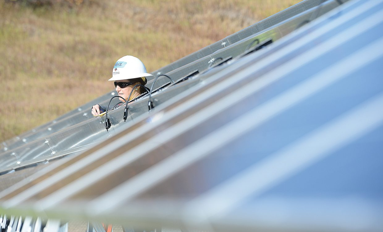 Yampa Valley Electric Association employee Kelli Root helps build a new solar array near the YVEA's new headquarters on Routt County Road 129 in Steamboat Springs. The volunteers joined YVEA employees building that array, which will help lower electric bills of qualified low-income residents  n the service territory.