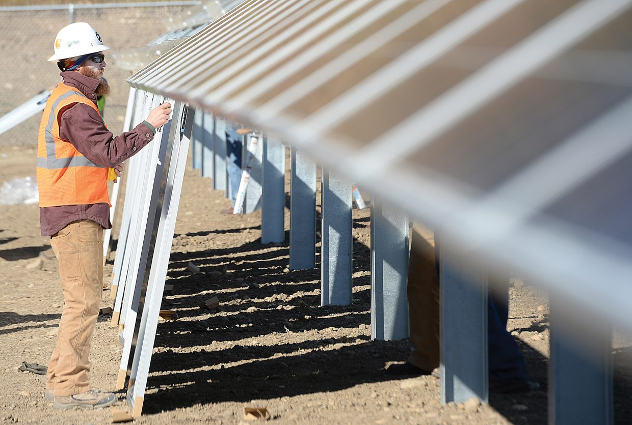 Paige Cofrin, a solar panel technician for GRID Alternatives, prepares solar panels before they are installed.