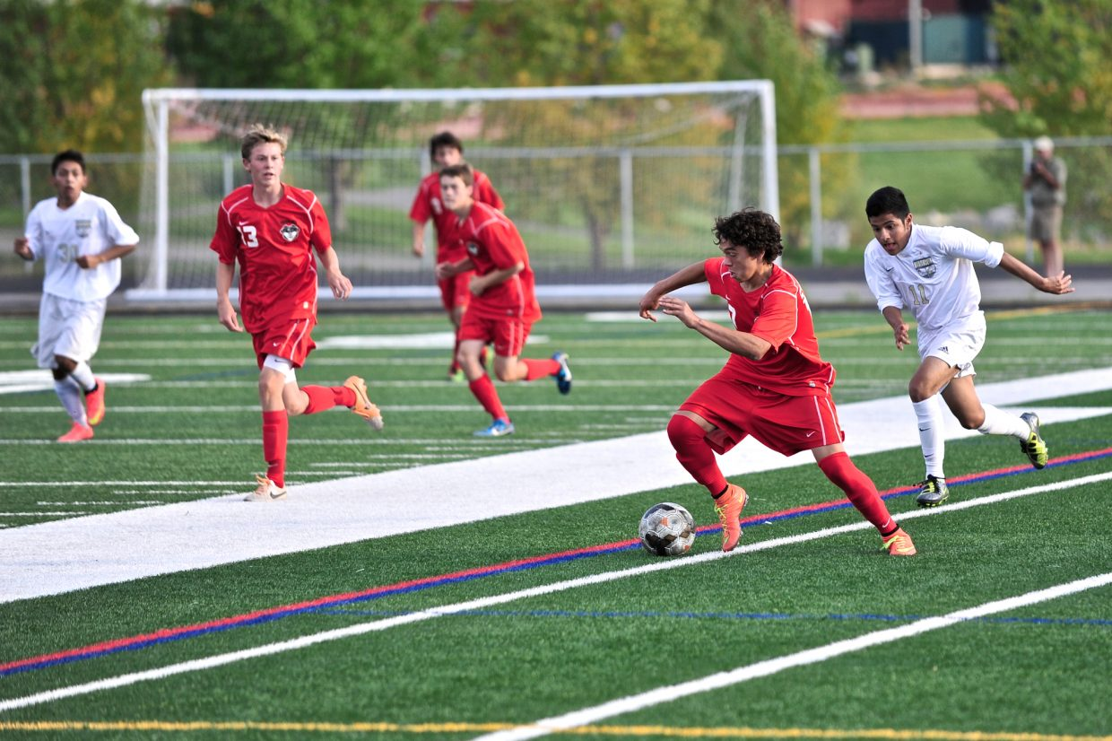 Steamboat's Cruz Archuleta drives the ball downfield while pursued by Battle Mountain's Uriel Lopez in Edwards on Thursday. The Huskies defeated the Sailors, 2-1.