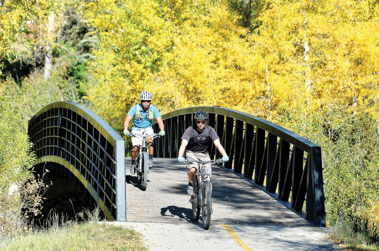 Todd Givnish, front, and Ed Briones make their way along the Yampa River Core Trail. Friday's warm temperatures made it the perfect day to get out and enjoy the changing colors in the Steamboat Springs area.