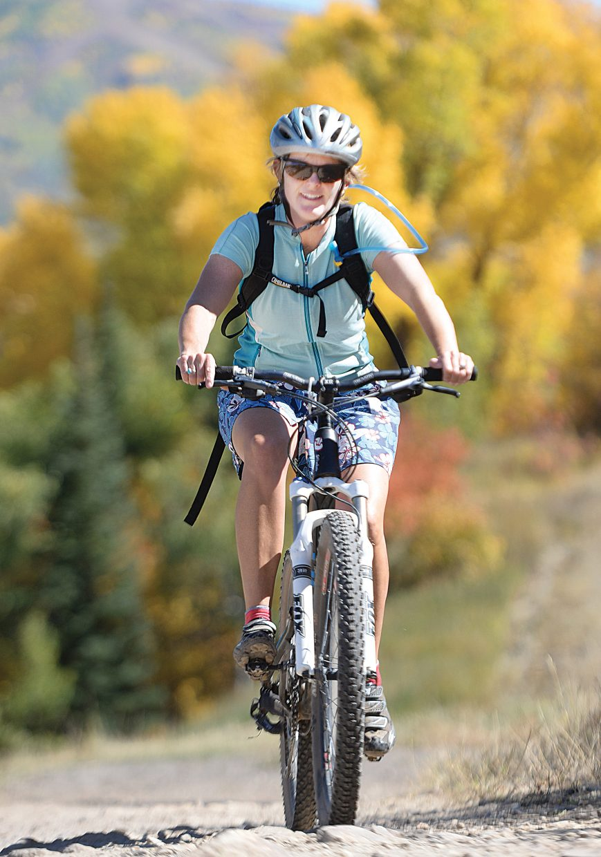 Steamboat Springs cyclist Megan Moore-Kemp rides on a trail at Howelsen Hill Monday afternoon. The warm temperatures may have made it feel like summer, but the colors in the background were proof that autumn has arrived.