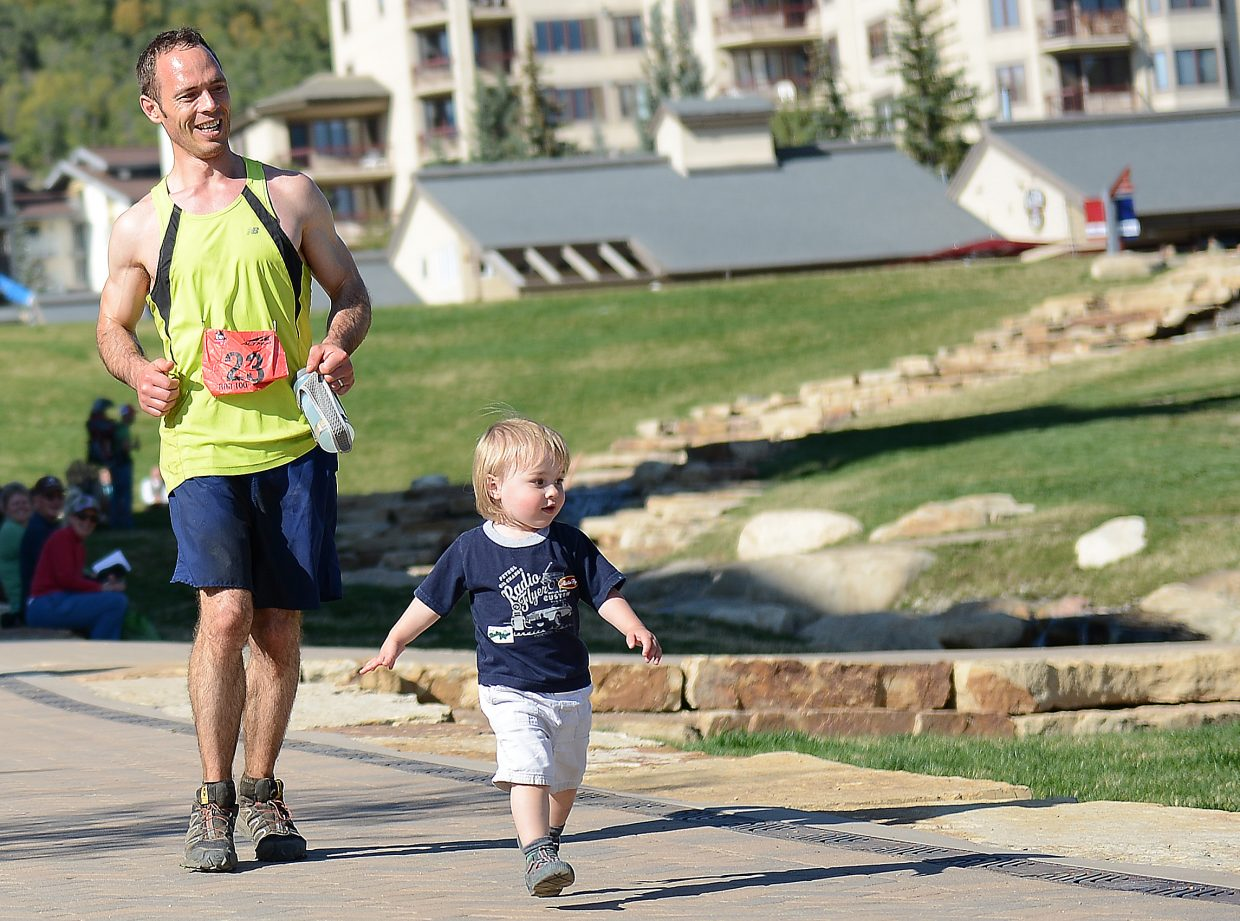 William Froehlich, right, leads his father — Run, Rabbit Run 100-mile finisher Bob Froehlich — into the finish line.