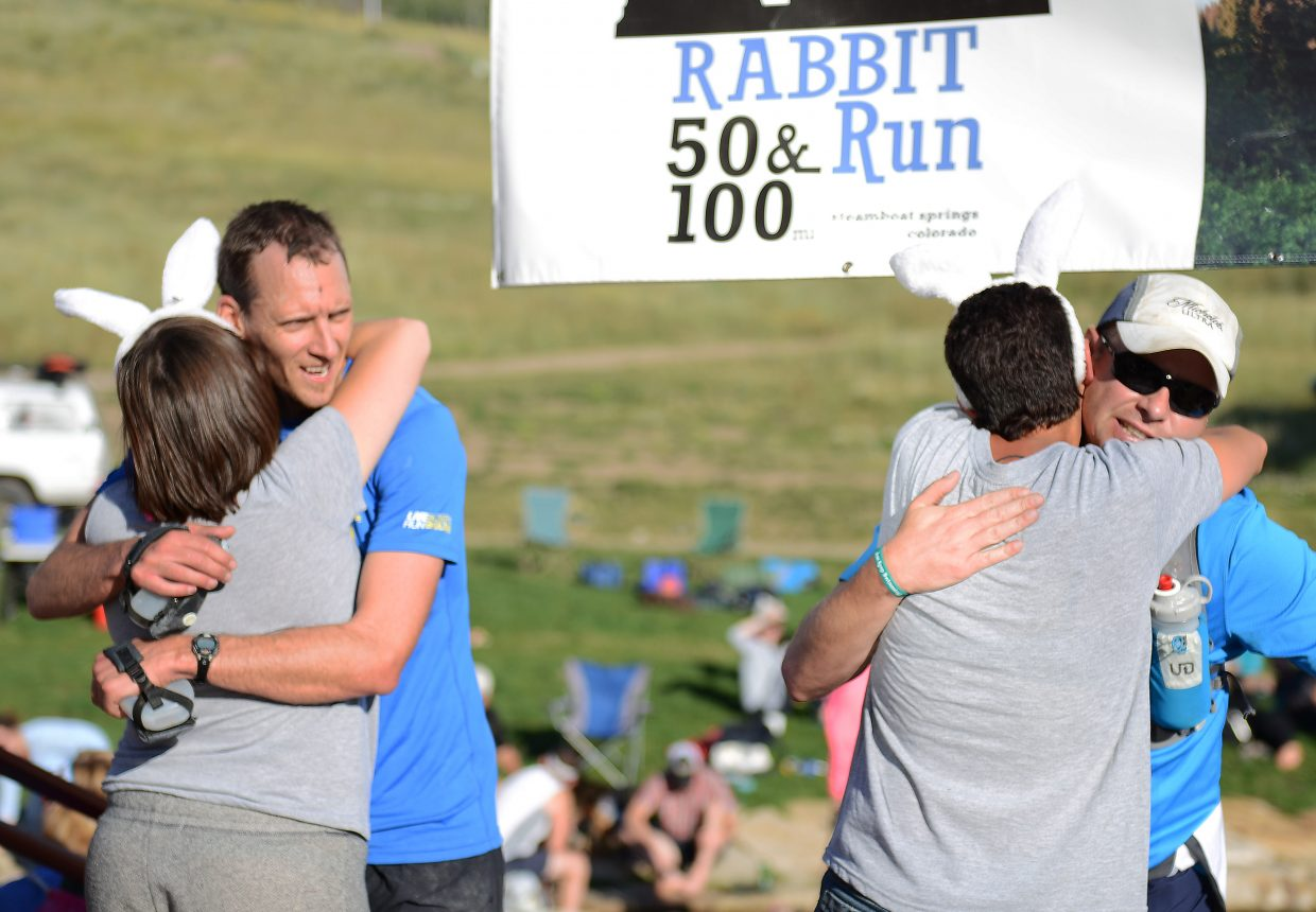 """Ashley Arroyo and Brady Worster deliver hugs at the finish line of the Run, Rabbit Run trail ultramarathon. The race has plenty of unique points. Among them is the """"hug and a mug"""" finish, a hug and a beer mug for race finishers."""