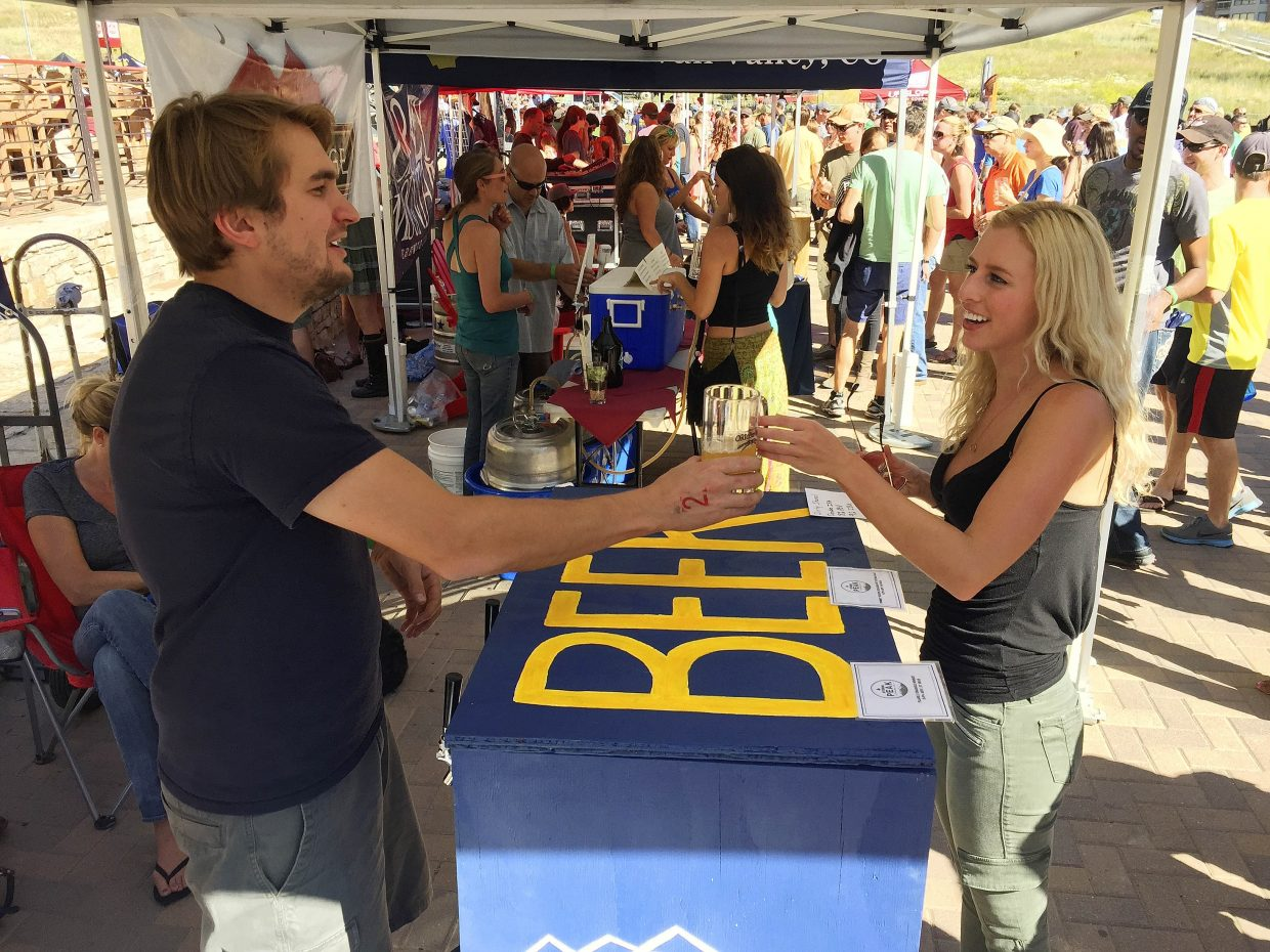 Storm Peak Brewing Company's Wyatt Patterson serves beer to Denver resident Christy Clark on Saturday during OktoberWest.