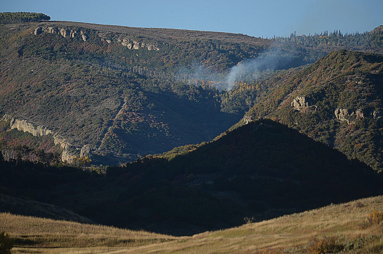 Smoke rises off the steep pitched slopes of Wolf Mountain Monday afternoon. Crews were able to use a single track road to get into the blaze and fight it. The blaze was contained on Tuesday.