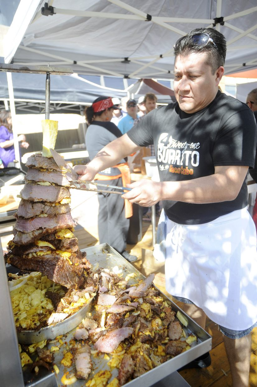 Saul Sandoval slices brisket for tacos at the Taco Cabo tent during OktoberWest on Saturday at the base of Steamboat Ski Area.